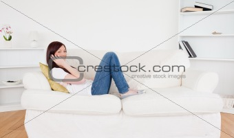 Beautiful red-haired woman having a conversation on the phone wh