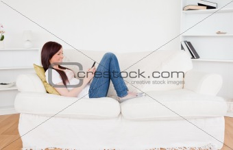 Attractive red-haired female writing a text on her phone while l