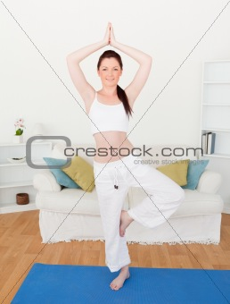 Attractive red-haired woman stretching in the living room