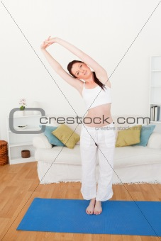 Charming red-haired woman stretching in the living room