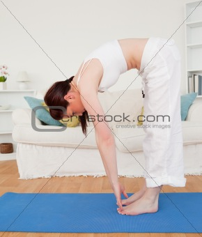 Attractive red-haired female stretching in the living room