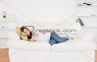 Attractive red-haired female watching tv while lying on a sofa