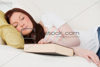 Beautiful red-haired girl having a rest while studying on a sofa
