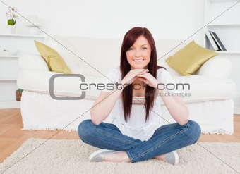 Beautiful red-haired woman posing while sitting on a carpet