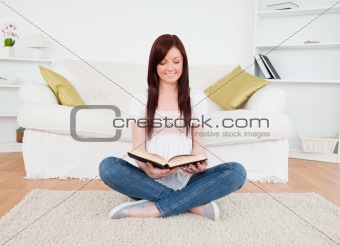 Beautiful red-haired female reading a book while sitting on a so
