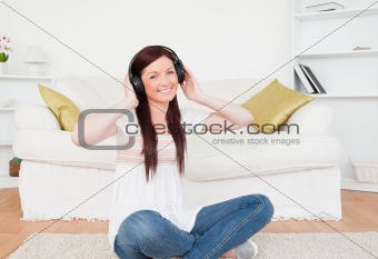 Attractive red-haired female listening to music with headphones