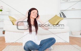 Beautiful red-haired female listening to music with headphones w