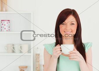 Charming red-haired woman having her breakfast in the kitchen