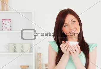 Attractive red-haired woman enjoying her breakfast in the kitche