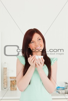Beautiful red-haired woman enjoying her breakfast in the kitchen