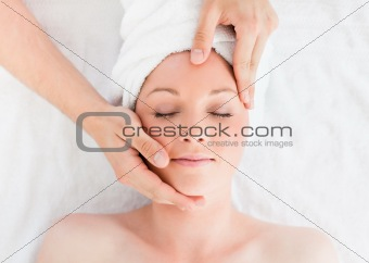 Closeup of a gorgeous red-haired woman receiving a massage in a spa centre