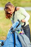 Laughing mother looking in stroller while walking in park
