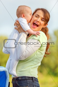 Baby kissing holding her happy mother