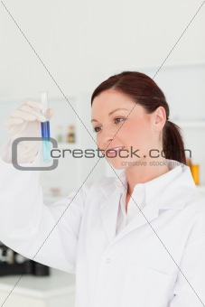 Attractive red-haired scientist looking at the camera while hold
