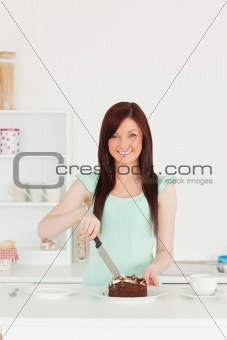 Beautiful red-haired woman cutting some cake in the kitchen