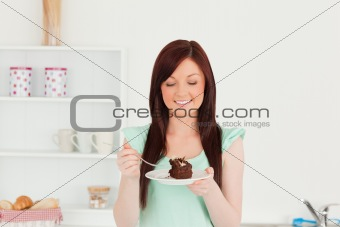 Beautiful red-haired woman eating some cake in the kitchen