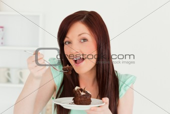 Charming red-haired woman eating some cake in the kitchen