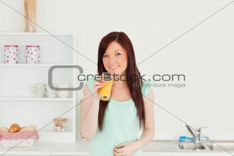 Beautiful red-haired woman enjoying a glass of orange juice in t