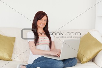 Attractive red-haired woman relaxing with her laptop while sitti