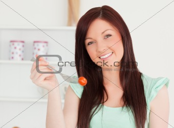 Attractive woman cutting eating a cherry tomato in the kitchen