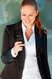 Smiling business woman near office building  looking on mobile