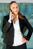 Pensive business woman talking on mobile  near office building