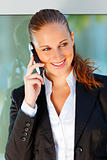 Portrait of smiling business woman talking on mobile at office building