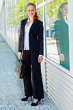 Full length portrait of smiling business woman with briefcase at office building