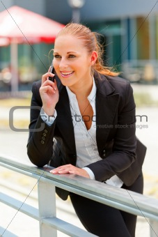Smiling business woman leaning on railing and talking on mobile