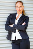 Concentrated business woman standing at office building