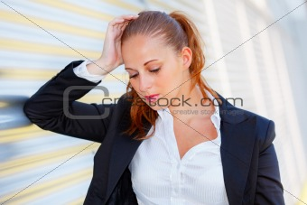 Tired business woman standing at office building and looking down