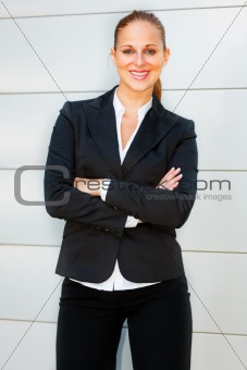 Smiling business woman with crossed arms on chest standing at office building