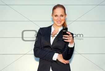 Smiling  business woman holding mobile in hand near office building