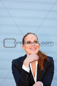 Smiling business woman at office building  looking up at copy-space