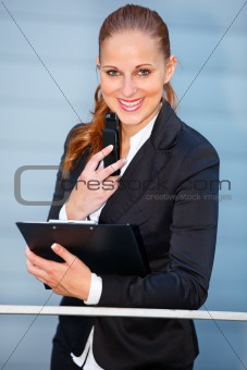 Leaning on railing at office building  smiling business woman holding mobile and clipboard