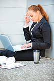 Concentrated business woman sitting on floor at office building laptop
