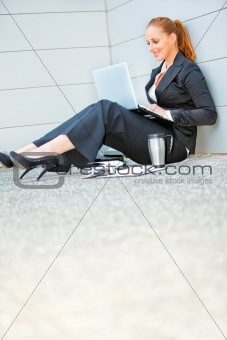 Smiling business woman sitting on floor at office building  and using laptop