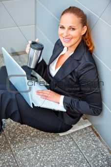 Smiling business woman with laptop and cup sitting on floor at office building