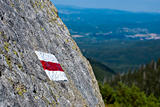 red mark of the tourist track on the stone in mountain