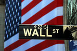 Street sign for Wall Street with the American Flag at the background
