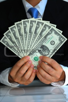 A gentleman holding a bunch of United States $2 dollar bills