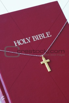 A golden cross on the top of a red bible