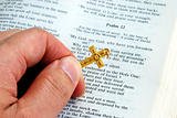 Holding a golden cross while reading the bible