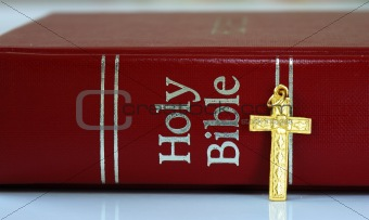 A golden cross next to the red bible