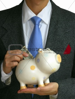 A gentleman deposits some money into the piggy bank