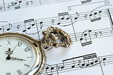 Antique pocket watch on the music sheet