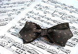 A gray bow tie on the top of music sheets