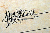 "Close-up view of the phrase ""Pay To The Order Of"""