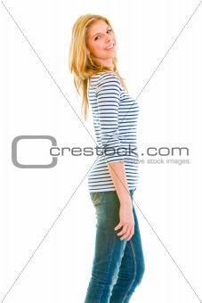 Portrait of smiling beautiful teen girl standing profile