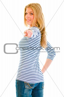 Smiling beautiful teen girl looking back and pointing finger at you